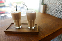 Deux boissons de café dedans dans la tasse en verre avec le support de paille à boire dessus images libres de droits