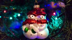 Deux bonhommes de neige accrochent sur l'arbre Photographie stock libre de droits
