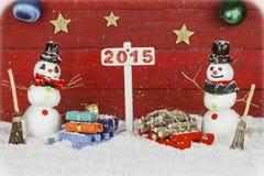 Deux bonhommes de neige et un poteau indicateur avec le nombre 2015 Images stock