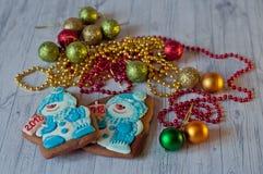 Deux bonhommes de neige gentils de pain d'épice s'étendant sur la table en bois avec des décorations de Noël Image stock