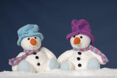 Deux bonhommes de neige mignons se reposant dans la neige Photo stock