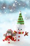 Deux bonhommes de neige se tenant dans la neige Image stock