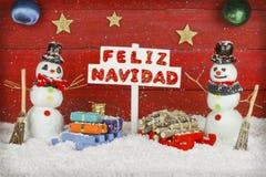 Deux bonhommes de neige tenant un signe avec le Joyeux Noël de mots écrit sur l'Espagnol Images libres de droits