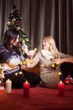 Deux bons amis féminins à côté d'un havin décoré d'arbre de Noël Photos stock