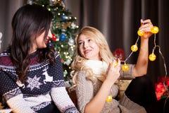Deux bons amis féminins à côté d'un havin décoré d'arbre de Noël Image stock