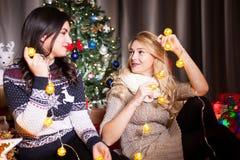 Deux bons amis féminins à côté d'un havin décoré d'arbre de Noël Photos libres de droits