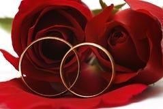 Deux boucles de mariage et roses rouges. Photographie stock