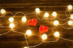 Deux bougies de forme de coeur parmi les lanternes rougeoyantes faites de rotin sur un fond en bois Images stock