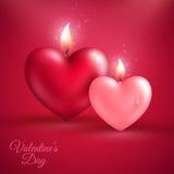 Deux bougies de forme de coeur sur le fond rouge Photo libre de droits