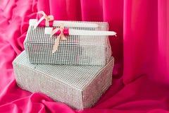 Deux bougies et boîtes sur le fond rose de tissu vacances Image stock