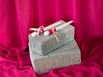 Deux bougies et boîtes sur le fond rose de tissu vacances Image libre de droits