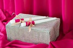 Deux bougies et boîtes sur le fond rose de tissu vacances Photo stock