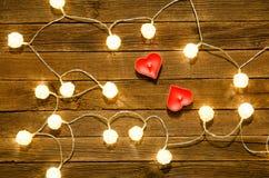 Deux bougies sous forme de coeur parmi les lanternes rougeoyantes faites de rotin sur un fond en bois Image libre de droits