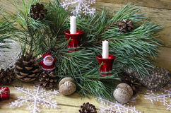 Deux bougies sur le pin s'embranchent avec les cônes et la Santa Claus Image libre de droits