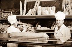Deux boulangers au compteur à la boulangerie image stock