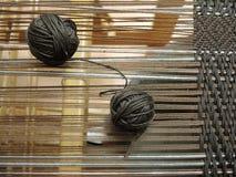Deux boules de fil avec des bandes de roulement sur le métier à tisser Image stock