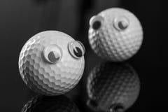 Deux boules de golf avec les yeux en plastique Photographie stock
