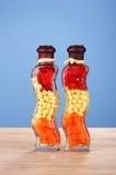 Deux bouteilles avec le poivron rouge, haricots, raccords en caoutchouc Photos stock