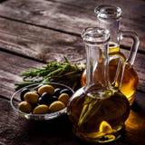 Deux bouteilles d'huile d'olive, d'olive dans une cuvette et d'herbes sur une table en bois Photos stock