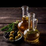 Deux bouteilles d'huile d'olive, d'olive dans une cuvette et d'herbes sur une table en bois Images stock