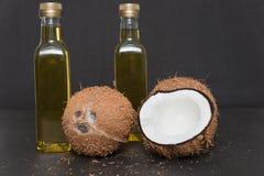 Deux bouteilles d'huile de noix de coco d'isolement sur le noir Images libres de droits