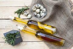Deux bouteilles d'huile d'olive avec le citron et le poivre se trouvant sur une lumière Image stock