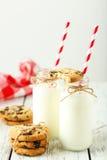 Deux bouteilles de lait avec les pailles et les biscuits rayés sur le fond en bois blanc Photographie stock
