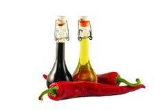 Deux bouteilles de vinaigre de vin, d'huile d'olive et de pe deux frais d'un rouge ardent Photo libre de droits