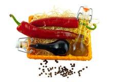 Deux bouteilles de vinaigre de vin, d'huile d'olive et de pe deux frais d'un rouge ardent Image libre de droits