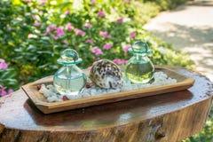 Deux bouteilles en verre avec des huiles aromatiques et coquille de mer sur l'étagère en bois Image libre de droits