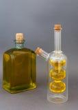 Deux bouteilles en verre avec l'huile d'olive sur un fond foncé Photo stock