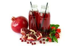 Deux bouteilles en verre du jus de grenade, du fruit, des graines et de la branche fleurissante de l'arbre de grenade d'isolement Photos stock