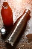 Deux bouteilles thermo inoxydables sur une table en bois ont pulvérisé avec de l'eau Avec l'effet de lumière du soleil image libre de droits
