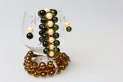 Deux bracelets faits main avec des boucles d'oreille dans un verre de cognac sur l'OIN Images stock