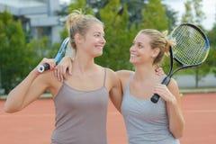 Deux bras de femme autour de l'un l'autre sur le court de tennis Photo stock