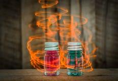 Deux breuvages magiques en verre magiques avec le liquide bleu et rouge sur la table en bois avec l'effet magique jaune Photo stock