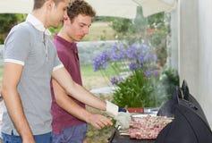 Deux brochettes de viande de cuisinier de garçons sur le barbecue Image libre de droits