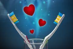 Deux brosses à dents sur un fond bleu et beaucoup de coeurs rouges Photo stock