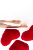 Deux brosses dentaires beiges avec les coeurs rouges sur le fond blanc D'isolement Amour Jour de Valentine Vue supérieure Copiez  Photo libre de droits