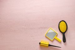 Deux brosses jaunes de crête de peigne de cheveux avec la poignée pour tous les types et le miroir de poche sur la copie rose esp Photographie stock