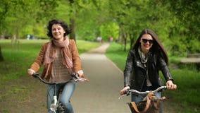Deux brunes montent par le parc de ville Belles brunes avec des bicyclettes appréciant Sunny Weather chaud banque de vidéos
