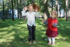 Deux bulles de savon de crochet de petites filles parmi des arbres Images stock