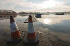 Deux cônes du trafic se reposent sur un passage couvert empêchant des personnes allant près d'un lac congelé photo libre de droits