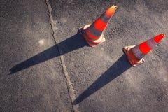 Deux cônes oranges de route sur l'asphalte gris Images libres de droits