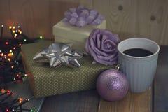 Deux cadeaux, tasse de café, une rose, une boule, lumières sur le tablennn Images libres de droits