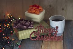 Deux cadeaux, une tasse de café et l'inscription marient Christmasn Photographie stock