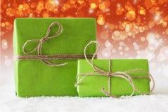 Deux cadeaux verts sur la neige, effet rouge complémentaire de Bokeh image libre de droits