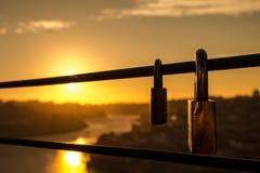 Deux cadenas coincés sur le pont au coucher du soleil images stock