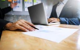 Deux cadres commerciaux analysant le papier de données au lieu de réunion images stock