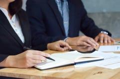 Deux cadres commerciaux analysant le papier de données au lieu de réunion photo libre de droits